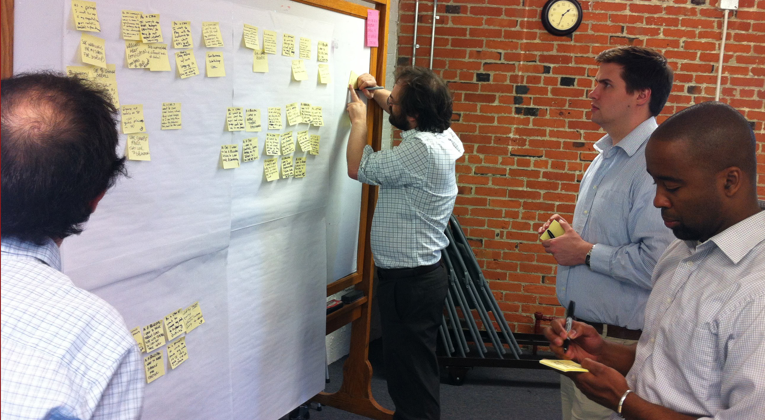 Green River engineers and clients doing a post-it design exercise on a big whiteboard