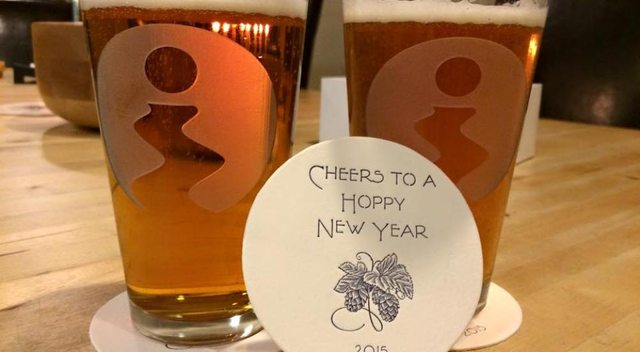 Etched pint class with green river logo and coaster that says Cheers to a Hoppy New Year